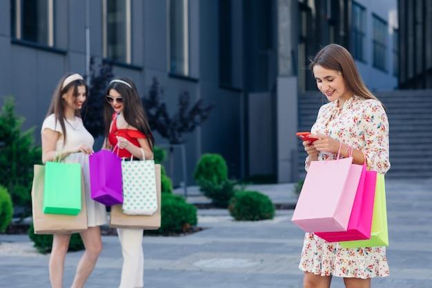 Happy shopping vrouw met een groep vrienden op de achtergrond. retail-, gebaar- en verkoopconcept. glimlachende tiener met veel boodschappentassen in winkelcentrum.
