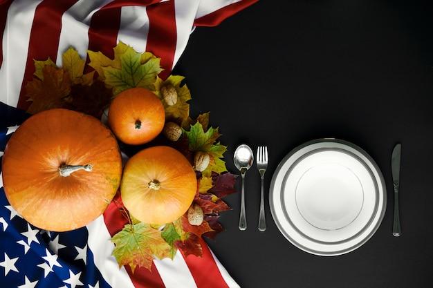 Happy thanksgiving tabel instelling. pompoenen met fruit, groenten, walnoten en vallende bladeren.