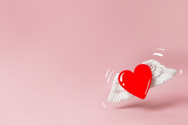 Happy valentijnsdag banner. een rood houten hart met witte volumineuze vleugels zweeft over een roze verfrommeld papier achtergrond. minimalisme. plaats voor tekst