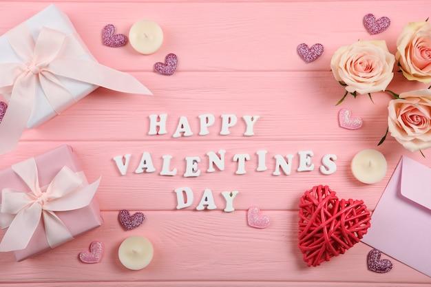 Happy valentijnsdag tekst met geschenken en decoraties op roze achtergrond