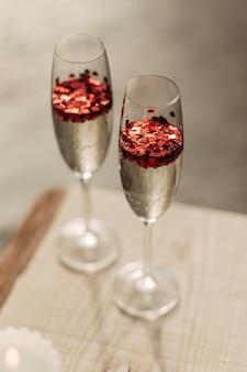 Happy valentijnsdag viering concept. close-up van 2 twee glazen met sprankelende champagne en rode hartvormige confetti. liefdesdrankje in glas. het concept van bruiloft, geliefden dag. romantische date