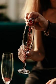 Happy valentijnsdag viering concept. man hartvormige confetti gieten in lege champagne glas van de vrouw. liefdesdrankje in glas.