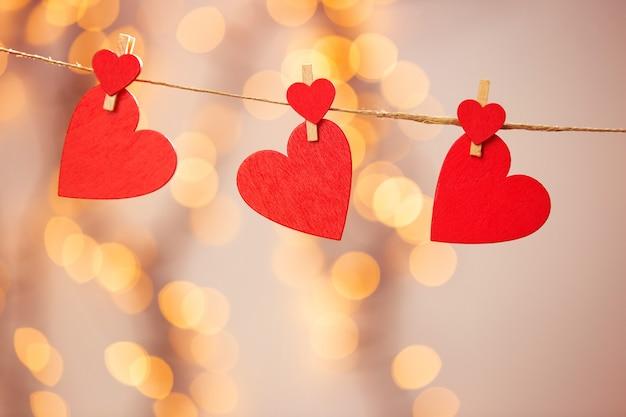 Happy valentine-dag met rode harten hangt met wasknijpers aan touw en bokeh lichten