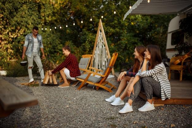 Happy vrienden bereidt zich voor op het koken op kampvuur, picknick op camping in het bos