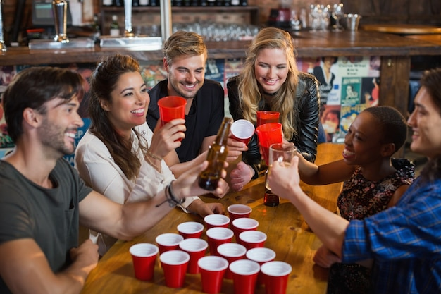 Happy vrienden bier drinken zittend rond wegwerp bekers in bar