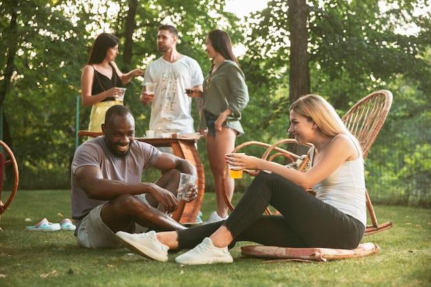 Happy vrienden eten en drinken van bier bij barbecue diner op zonsondergang tijd