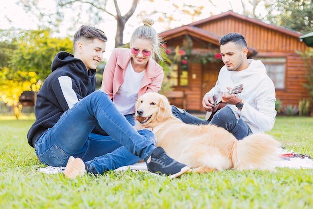 Happy vrienden genieten van ukelele muziek en het buitenleven - groep vrienden zittend op het gras met een charmante hond.