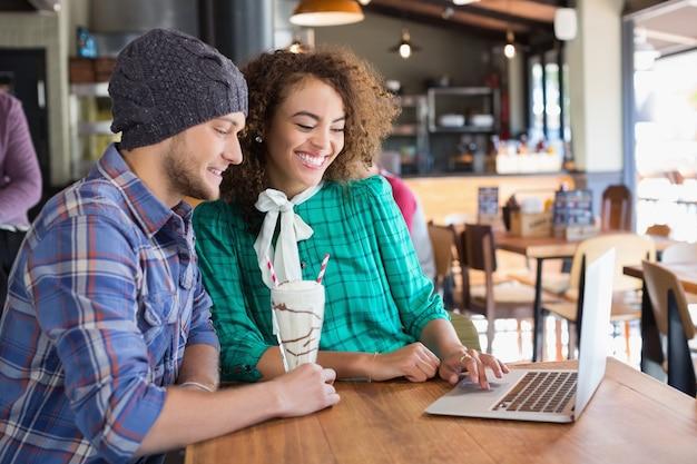 Happy vrienden met behulp van laptop aan tafel in restaurant