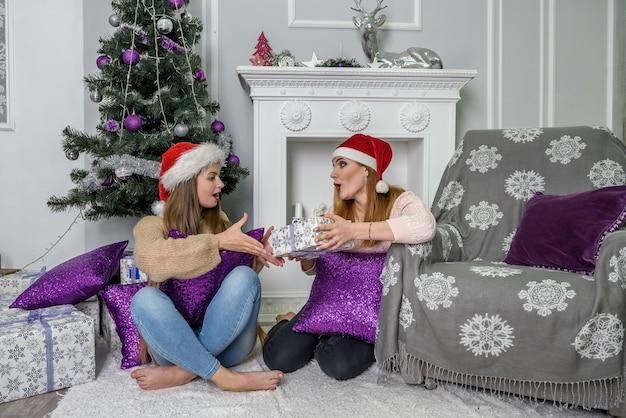 Happy vrienden poseren in de buurt van kerstboom in studio