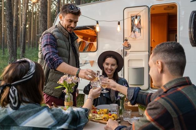 Happy vrienden rammelende glazen wijn over de geserveerde tafel