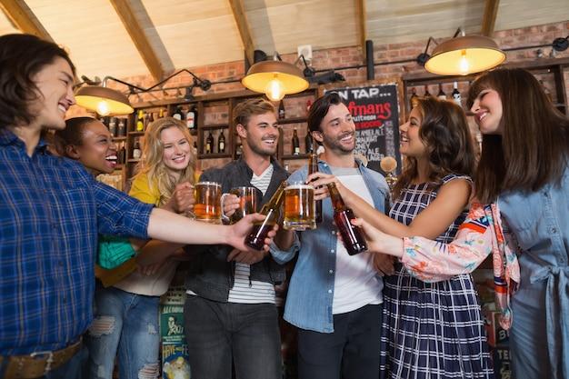 Happy vrienden roosteren bierglazen en flessen in de pub