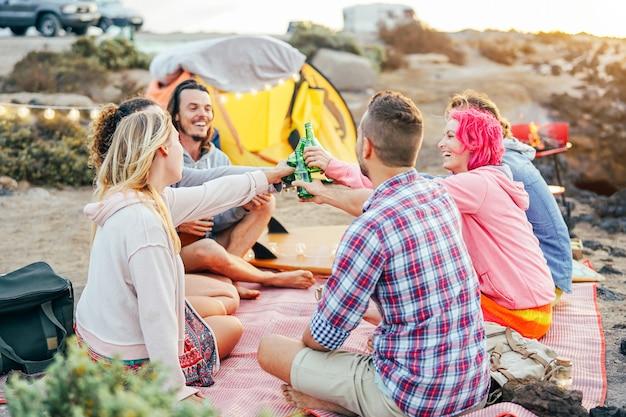 Happy vrienden roosteren met bieren bij barbecue diner op het strand