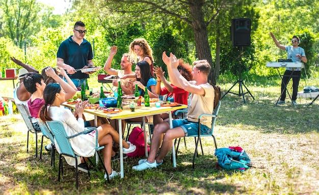 Happy vrienden samen plezier op barbecue pic nic party - multiraciale jongeren op openlucht food festival - vriendschap jeugdconcept met jongens en meisjes eten op tuin barbecue