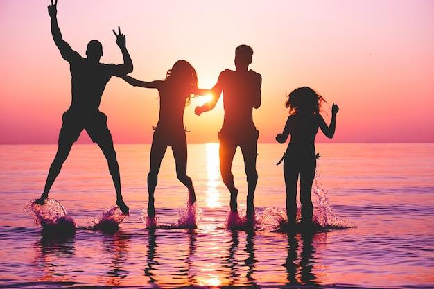 Happy vrienden springen in water op tropisch strand bij zonsondergang
