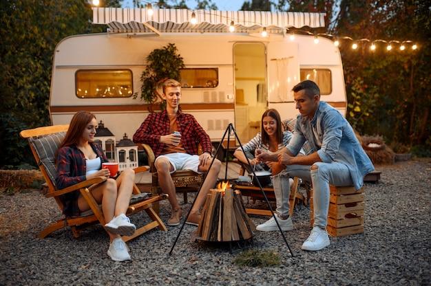 Happy vrienden zitten in de buurt van kampvuur in de avond, picknick op camping in het bos