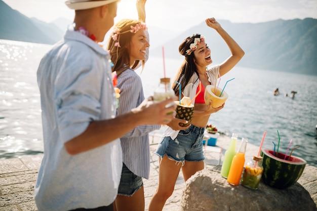 Happy vriendengroep plezier op strandfeest cocktail drinken bij zonsondergang. zomervreugde en vriendschapsconcept met jonge mensen op vakantie