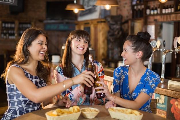 Happy vriendinnen houden roosteren bierflesjes