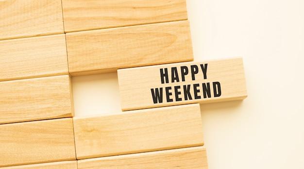 Happy weekend-tekst op een strook hout liggend op een witte tafel.