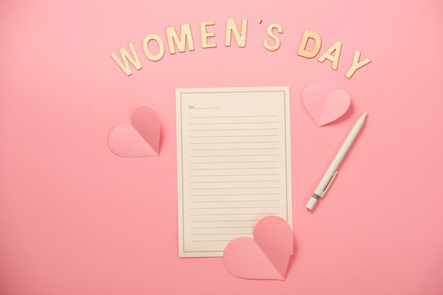 Happy woman's day-bericht met hartpapier op koraalpapierachtergrond