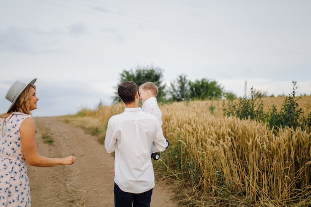 Happy young family vader, moeder en zoontje ziet er gelukkig uit in het park