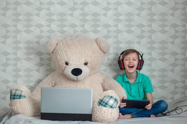 Happykid die in hoofdtelefoons op digitale tablet naast een stuk speelgoed spelen draagt bekijkend een computer.