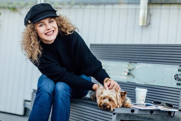 Happypretty womanl houdt haar mooie yorkshire terrier-hond vast terwijl ze op de stadsbank zit.