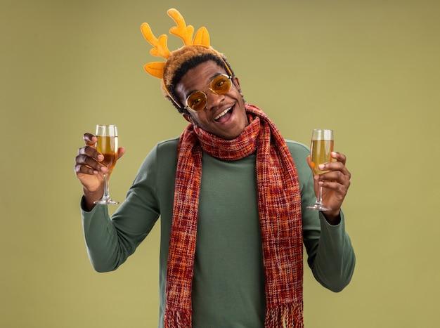 Hapy afro-amerikaanse man met grappige rand met herten hoorns en sjaal om de nek met twee glazen champagne glimlachend vrolijk staande over groene muur