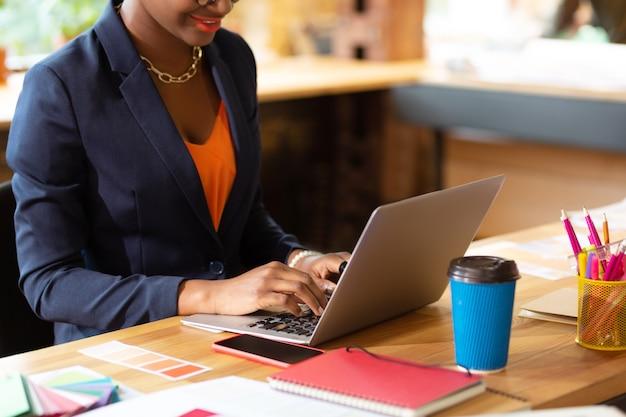 Hard aan het werk, interieurontwerper met heldere lippen die koffie drinkt en op laptop werkt