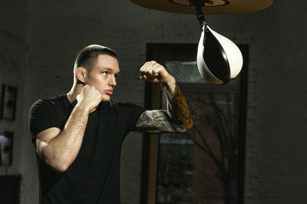 Hard aan het werken. shot van een knappe jonge bokser die traint met de speedbag in de sportschool