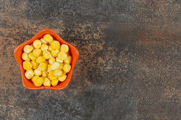 Hard geel suikergoed in oranje kom.