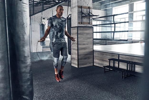 Hard pushen om te winnen. volledige lengte van jonge afrikaanse man in sportkleding springtouw