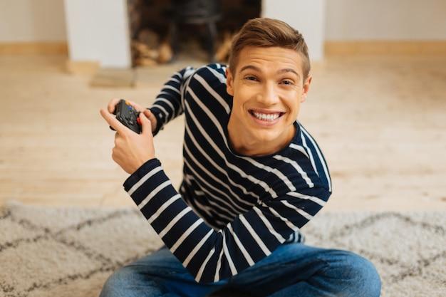 Hard spelen. knappe opgewonden blonde jongeman glimlachend en met een afstandsbediening voor games zittend op de vloer