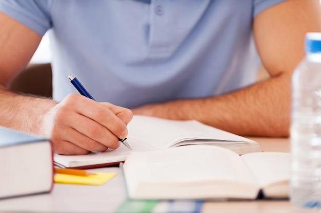 Hard studeren. bijgesneden afbeelding van student die iets in notitieblok schrijft terwijl hij aan het bureau zit