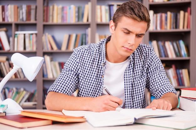 Hard studeren voor goede cijfers. zelfverzekerde jonge man die onderzoek doet terwijl hij in de bibliotheek zit