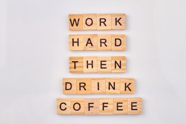 Hard werk concept. werk hard en drink dan koffie. alfabetkubussen met letters die op witte achtergrond worden geïsoleerd.