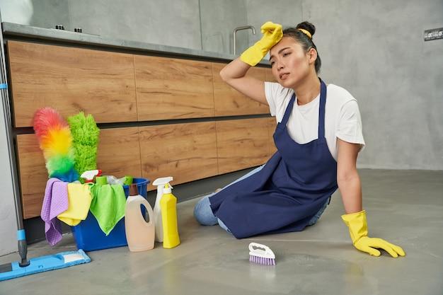 Hard werken full-length shot van vermoeide, uitgeputte jonge vrouw die uitrust tijdens het schoonmaken