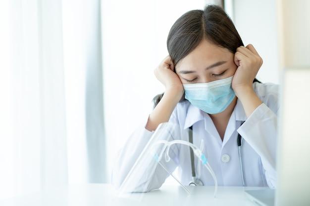 Hard werken van aziatische jonge vrouwelijke arts in het ziekenhuis, stressvol - workaholic gezondheidswerker in het ziekenhuis. medicatie werken moe van hard werken.
