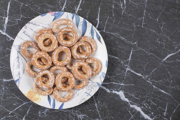 Harde gezouten pretzels op kleurrijke plaat.