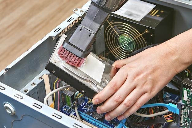 Harde schijf van personal computer wordt schoongemaakt door een draagbare stofzuiger.