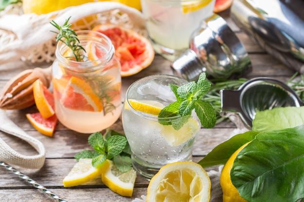 Harde seltzer-cocktails met citroen, grapefruit, munt, rozemarijn en ijs op een tafel. zomerse verfrissende drank, drankje met trendy zero waste-accessoires, bamboestro en netzak.