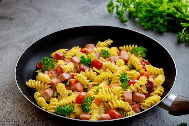Harde tarwe griesmeel pasta met tomaat, groene erwten in de pan