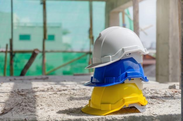 Harde veiligheidshelm voor ongevallenstapel op de vloer op de werkplek in de bouwplaats