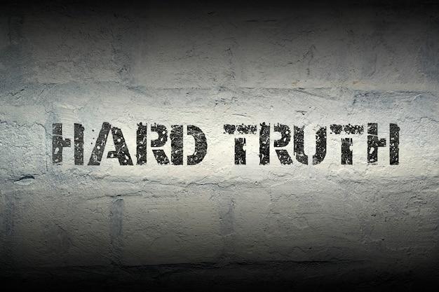 Harde waarheid zin stencil print op de grunge witte bakstenen muur
