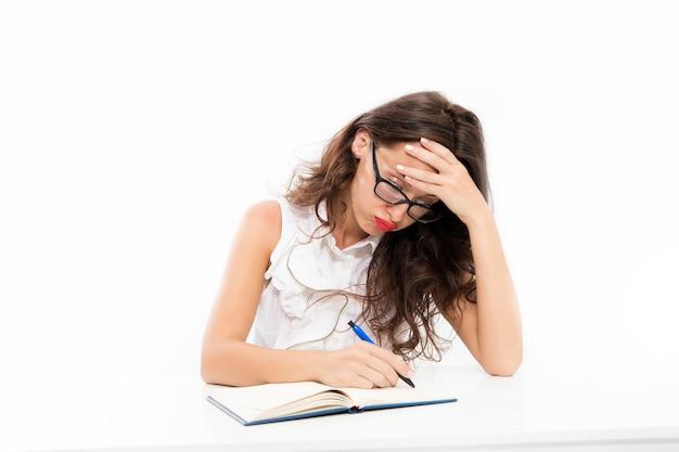 Harde werkdag. leerling druk aan het werk. terug naar school. geconcentreerd op les of examen. vrouw schrijft een essay. noteer belangrijke informatie. grote hoeveelheid werk. drukke overwerkte vrouw zit aan tafel.