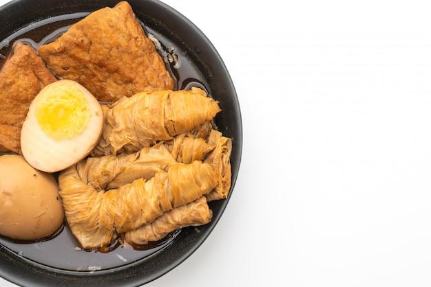 Hardgekookt ei in bruine saus of zoete jus op wit wordt geïsoleerd
