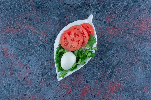 Hardgekookt ei met gesneden tomaat en kruiden.
