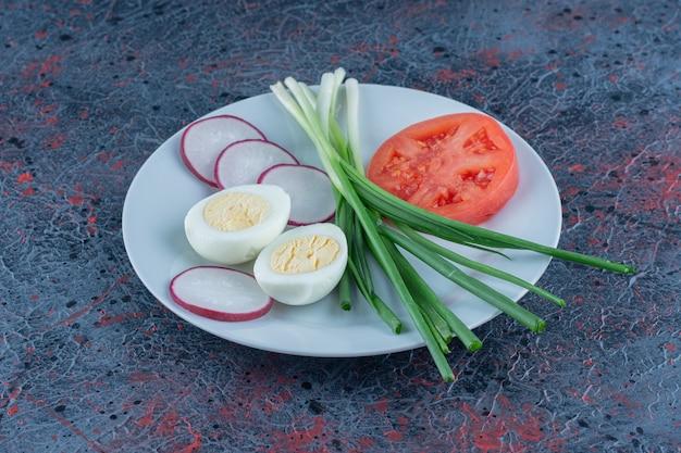 Hardgekookt ei met gesneden tomaat en radijs.