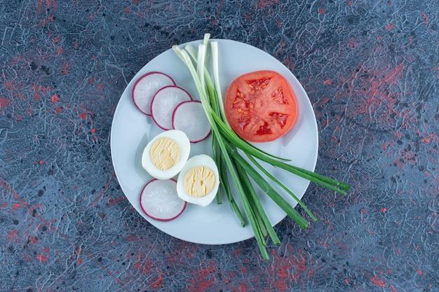 Hardgekookt ei met gesneden tomaat en radijs