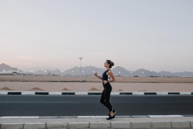 Hardlopen, trainen op de weg in de vroege ochtend van vrolijke mooie vrouw. opleiding van een sterke sportvrouw, energie, motivatie, gezonde levensstijl, opgewekte stemming.