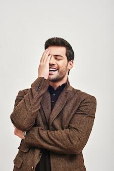 Hardop lachen jonge man die zijn gezicht bedekt met de hand en lachen geïsoleerd op een